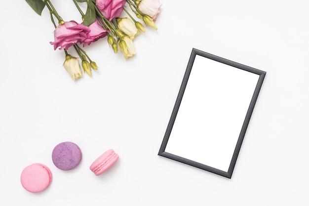 Fleurs roses avec cadre vierge et macarons Photo gratuit