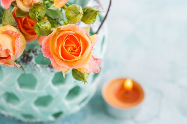 Fleurs De Roses Orange Fraîches Dans Un Vase à La Menthe Et Une Bougie Allumée Photo Premium