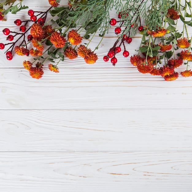 Fleurs rouges avec des baies dispersées sur une table en bois Photo gratuit