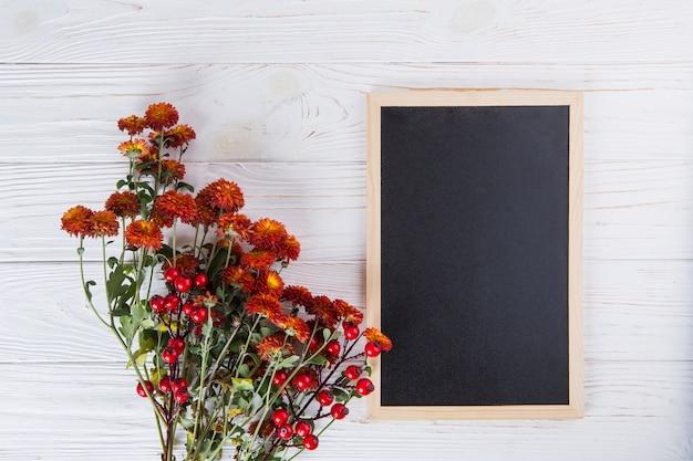 Fleurs rouges avec tableau blanc sur table en bois Photo gratuit