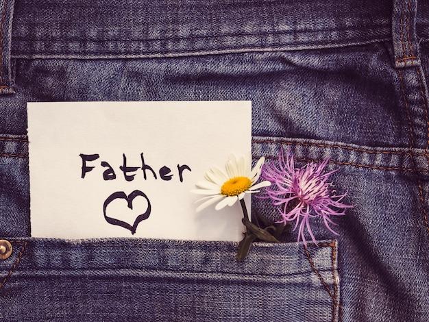 Fleurs sauvages et note en papier avec le mot père Photo Premium