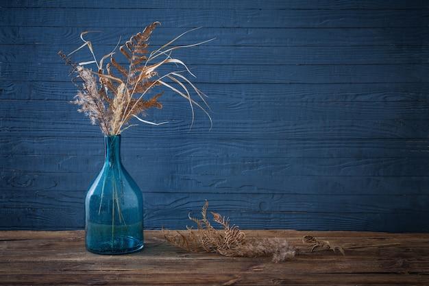 Fleurs Séchées Dans Un Vase En Verre Sur Table En Bois Sur Fond Bleu Photo Premium