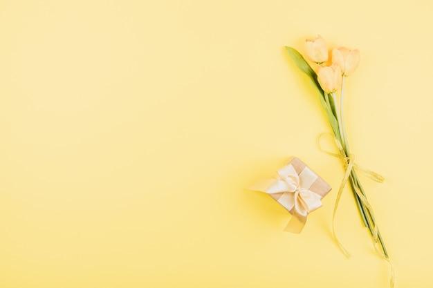 Fleurs de tulipes jaunes et coffret cadeau sur fond pastel. anniversaire de fête posé à plat Photo Premium