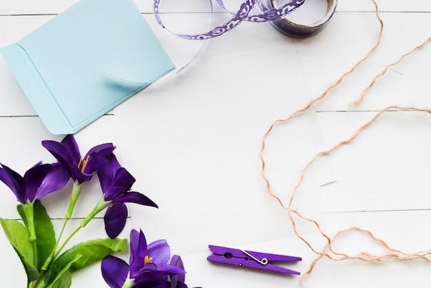 Fleurs violettes artificielles faites à la main; papier; ruban; pince à linge et ficelle sur fond de planche blanche Photo gratuit