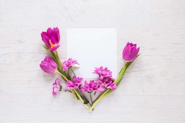 Fleurs violettes avec du papier vierge sur la table Photo gratuit