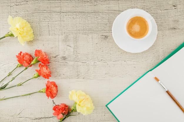 Fleurs de vue de dessus avec livre et café sur fond en bois Photo gratuit