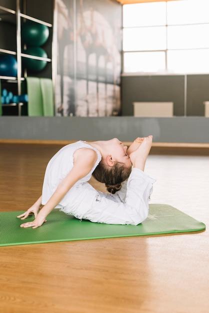 Flexible petite fille enfant exerçant sur tapis vert dans la salle de gym Photo gratuit