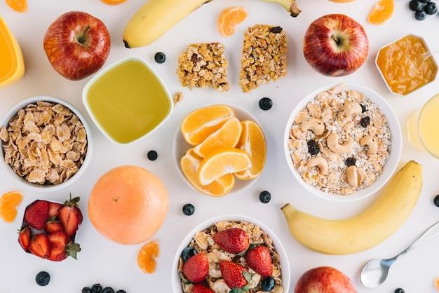 Flocons d'avoine dans des bols avec des fruits et des baies sur une table blanche Photo gratuit