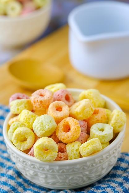 Flocons De Céréales Dans Un Bol Blanc Avec Espace Copie, Concept De Petit-déjeuner. Nourriture Avec Un Délicieux Goût Fruité Et Des Couleurs Fruitées Photo Premium