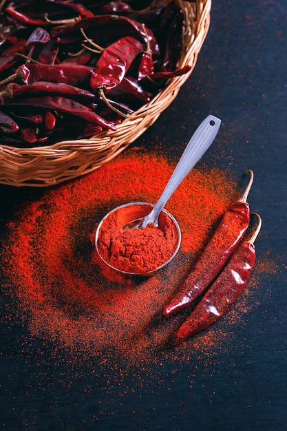 Des flocons de piment rouge et de la poudre de chili éclatent sur fond noir Photo Premium