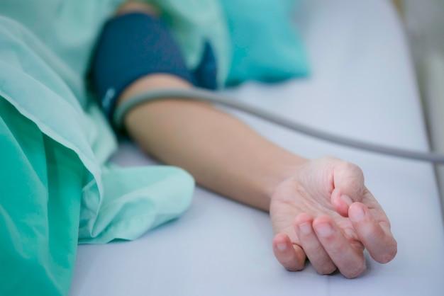 Flou artistique de la main du patient mesurant la pression artérielle à l'hôpital. concept de santé, d'hôpital et de médecine - Photo Premium