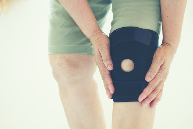 Flou artistique de vieilles femmes asiatiques à une blessure au genou sur fond blanc Photo Premium
