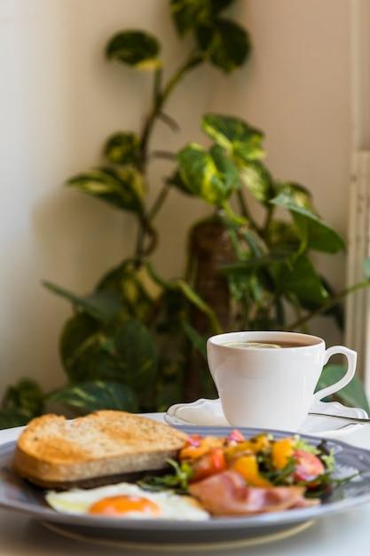Flou du petit-déjeuner et du thé sur la table devant les plantes Photo gratuit