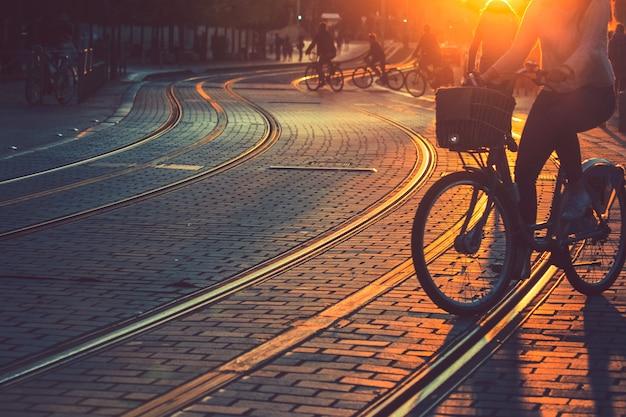 Flou de gens à vélo pendant le coucher du soleil dans la ville de bordeaux dans le style vintage et la texture du grain avec espace de copie Photo Premium