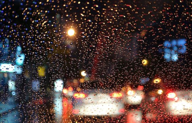 Flou de véhicules et de feux arrière vus à travers les gouttes de pluie sur le pare-brise d'une voiture la nuit Photo Premium