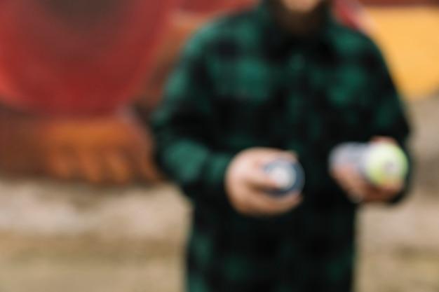 Floue homme tenant aérosol aérosol peut dans la main Photo gratuit