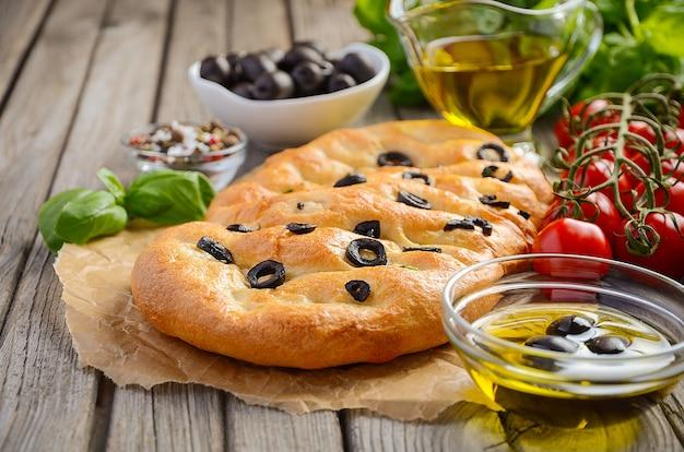 Focaccia italien pain aux olives et romarin sur fond en bois rustique. Photo Premium