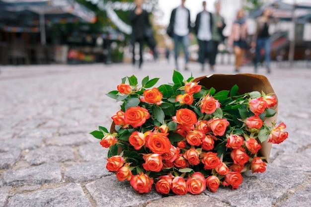 Focus Sur Bouquet De Roses En Papier Kraft Sur Pavage Rue Grise Photo gratuit