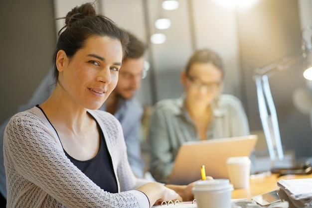 Focus sur la jolie brune en regardant la caméra dans un espace de travail co Photo Premium