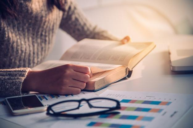 Focus livre ouvert à la main pour lire sur le travail de bureau avec un éclairage doré le matin Photo Premium