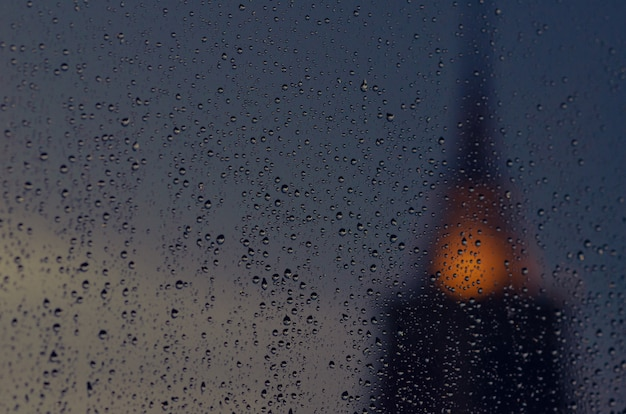 Focus partiel de la pluie tombe sur la vitre en saison de la mousson avec une pagode floue du fond du temple. Photo Premium
