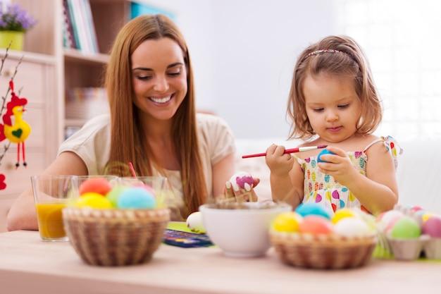 Focus Petite Fille Peignant Des Oeufs De Pâques Avec Sa Mère Photo gratuit