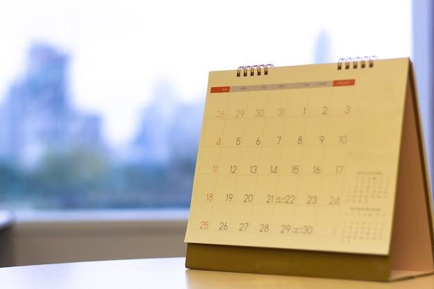Focus sélectionné calendrier sur la table avec un arrière-plan avec vue sur la ville Photo Premium