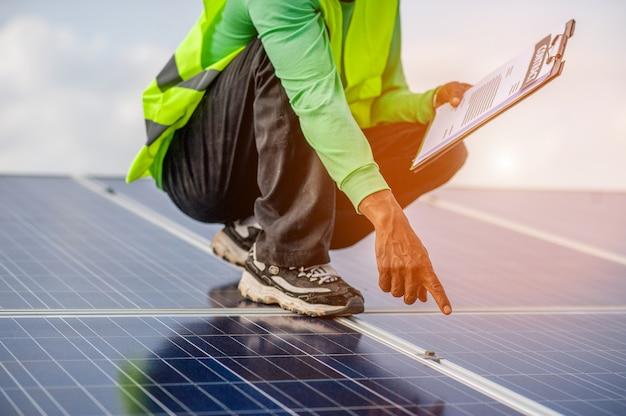 Les fonctionnaires travaillent sur les panneaux solaires, l'alimentation électrique alternative et l'espace au sol. énergie naturelle Photo Premium