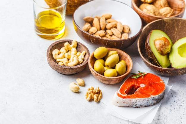 Fond d'aliments gras sains. poisson, noix, huile, olives, avocat sur fond blanc. Photo Premium