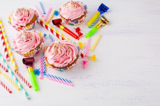 Fond d'anniversaire avec des gâteaux roses et des bougies d'anniversaire Photo Premium