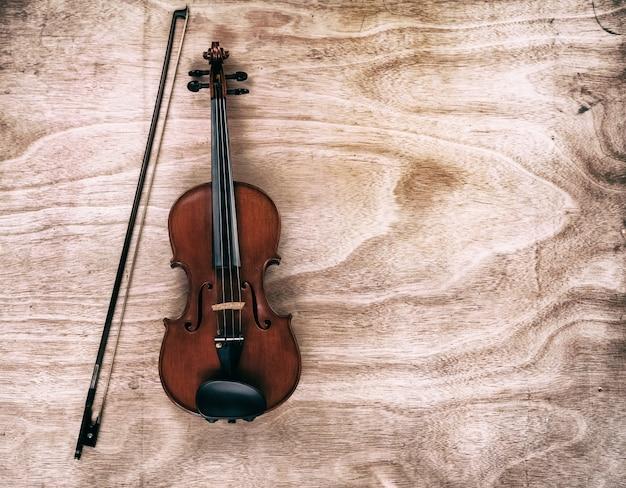 Le fond d'art abstrait de violon classique et archet mis sur une planche de bois Photo Premium