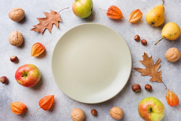 Fond d'automne avec les feuilles jaunes, pommes citrouilles poires et noix Photo Premium