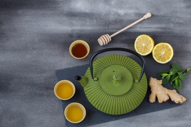 Sur un fond de béton, une théière sur un plateau, du thé dans un bol, du gingembre, du miel, de la menthe et du citron Photo Premium