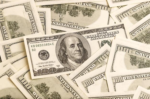 Un fond de billets de cent dollars dans un style vintage en mettant l'accent sur l'un des billets. Photo Premium