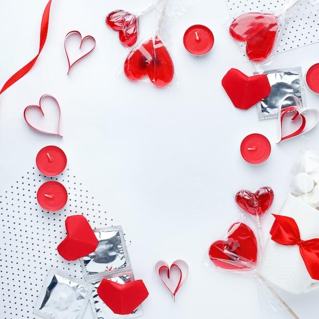 Fond blanc avec des coeurs rouges, des préservatifs, des cadeaux de douceur et des bougies. Photo Premium