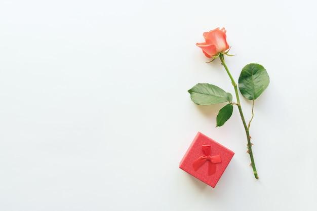 Fond blanc cosmétique beauté avec rouge à lèvres, boîte cadeau et rose Photo Premium