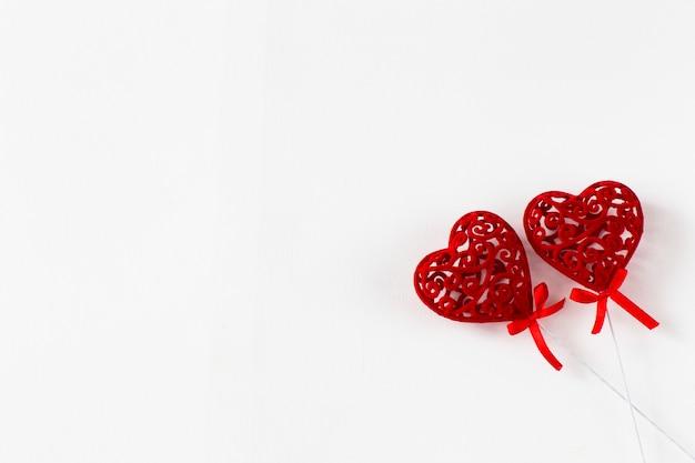 Sur fond blanc deux coeurs ajourés rouges Photo Premium