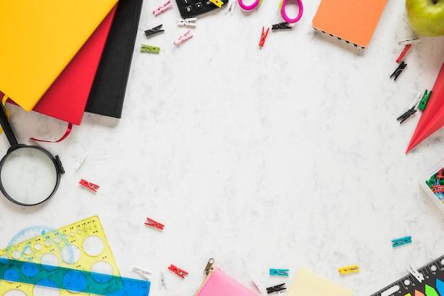 Fond blanc avec des fournitures scolaires et des manuels scolaires Photo gratuit