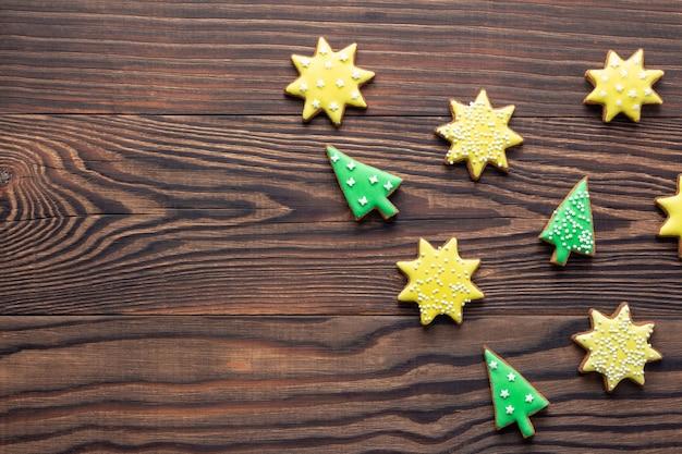 Fond En Bois De Noël Avec Des Biscuits Ou Des Pains D'épices En Forme D'étoiles Et D'arbres Avec Du Glaçage Photo Premium