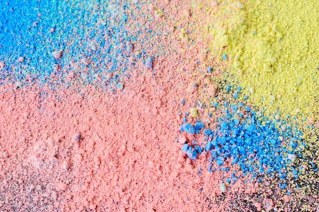 Fond coloré de poudre de craie. particules de poussière multicolores éclaboussées sur fond noir. Photo Premium