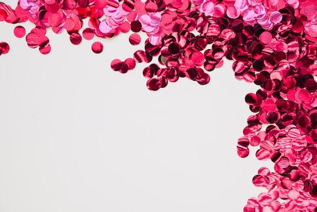 Fond avec des confettis brillants roses Photo gratuit