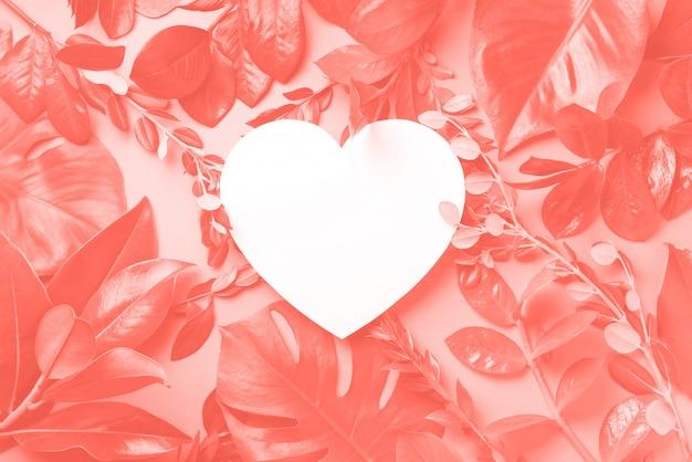 Fond créatif fait de feuilles tropicales, papier en forme de coeur de couleur corail. lay plat. vue de dessus. Photo Premium