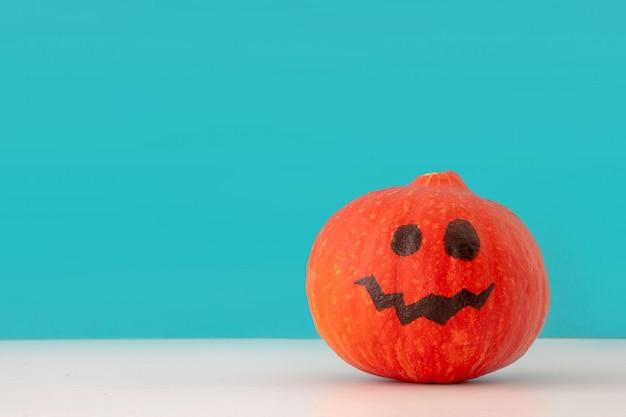 Fond créatif de vacances halloween avec citrouille jack o lantern sur fond bleu Photo Premium