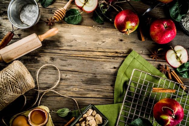 Fond De Cuisine Automne, Concept De Cuisson De Tarte Aux Pommes, Pommes Rouges Fraîches, épices Douces, Sucre, Farine, Rouleau à Pâtisserie, œufs, Ustensiles De Cuisson, Fond En Bois Photo Premium