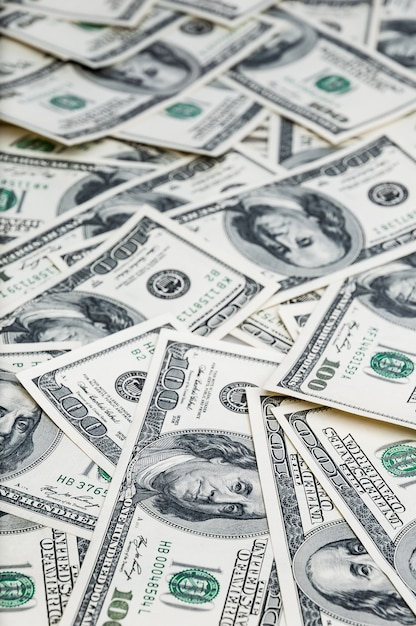 Fond de dollars. des billets de cent dollars américains sont éparpillés dans le fond. Photo Premium