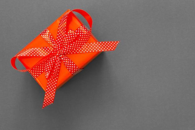 Fond De Fête Avec Cadeau, Boîte-cadeau Rouge Avec Ruban à Pois Et Arc Sur Fond Gris, Concept De Vendredi Noir, Mise à Plat, Vue De Dessus Photo Premium