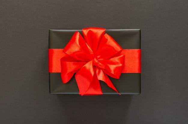 Fond De Fête Avec Cadeau, Coffret Cadeau Noir Avec Ruban Rouge Et Arc Sur Fond Noir, Concept De Vendredi Noir, Mise à Plat, Vue De Dessus Photo Premium