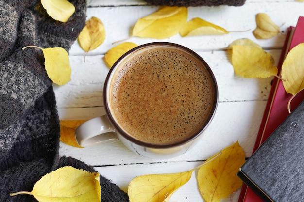 Fond avec des feuilles d'automne et une tasse de café chaud. feuilles d'automne tombées jaunes Photo Premium