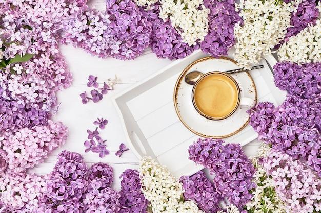 Fond de fleurs lilas avec une tasse de café au milieu Photo Premium