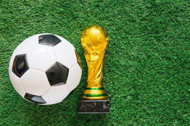 Fond de football sur l'herbe avec ballon et trophée Photo gratuit